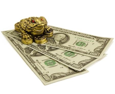 Feng Shui Money keeper frog sitting on money. Stock Photo