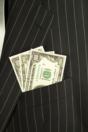 bolsa dinero: Dólares billetes de banco en un bolsillo de un traje de hombre de negocios.
