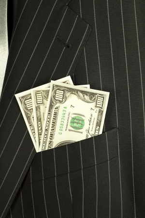 richer: Dollars banknotes in a pocket of a businessman suit.