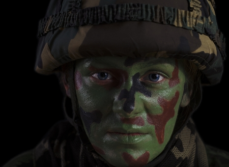 female soldier: Female Soldier in a Marine Helmet With Face Camouflage Against Dark Background Stock Photo