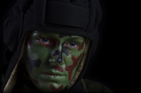 female soldier: Female Soldier in a Tank Helmet With Face Camouflage Against Dark Background