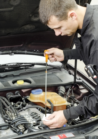 oleos: Mec�nico de Autom�viles Comprobaci�n del aceite del motor Foto de archivo