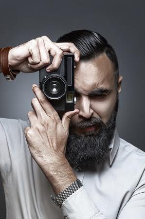 hombre disparando: Retrato del alto estilo de la moda de hombre con barba disparar con su cámara de la vieja escuela, estilo Esquire
