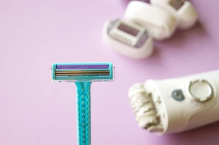 Closeup view with selective focus of disposable shaver isolated against the background of the epilator. Man and woman body treatment of depilation with razor and skin care concept. Epilation hair removal.
