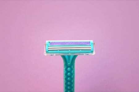 Closeup view with selective focus of disposable shaver isolated on abstract pink background. Man and woman body treatment of depilation with razor and skin care concept. Epilation hair removal.