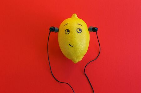 One lemon in the phone's headphones is enjoying music. Musical concept. 版權商用圖片