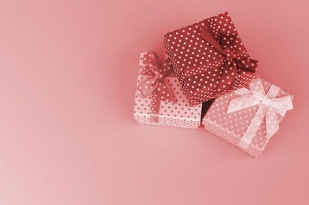 Wrapped Christmas or other holiday handmade present in paper with pink ribbon on coral background. Present box, decoration of gift on colored table, top view with copy space