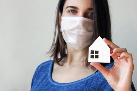Image of the face of a young woman in a medical mask with a paper house in her hand urging everyone to stay home during a pandemic and quarantine. Prevention of bacterial infection with coronavirus or Covid 19.