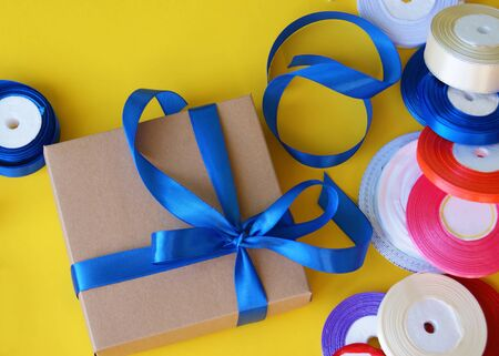 Gift box packaging on a yellow background. A lot of bright satin ribbons. 免版税图像