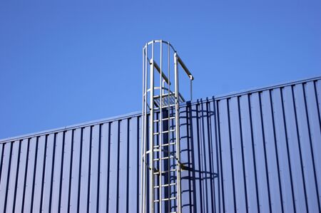 Blue background metal wall siding, cladding with stairs to the roof. Reflective metallic convex texture. Abstract ribbed backgrounds.