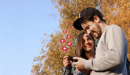 New alerts on a mobile phone, a happy young couple, opening social networks to view messages, likes, comments. Copy space.