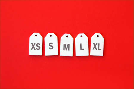 Various clothing sizes XS, S, M, L, XL on white wooden tags on a red background.
