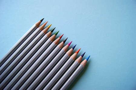 Many color pencils lies on light blue background. Art concept