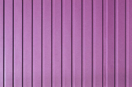 Pink background of metal wall siding, cladding. Reflecting metal convex texture. Abstract ribbed backgrounds.