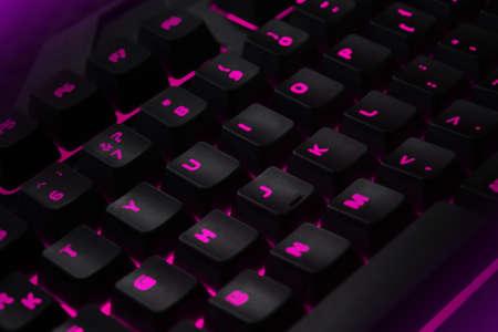 Backlit gaming keyboard close up. Black keys with pink illuminated characters. Фото со стока