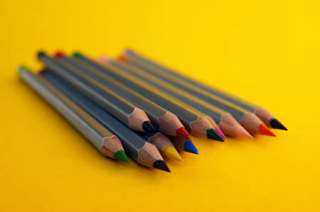 Many colorful pencils laying on a beautiful yellow background. Selective focus.
