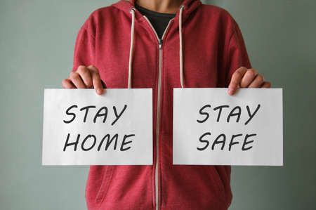 A young man is holding a paper with the words Stay home and Stay safe. The concept of self-defense and home awareness in social networks and the prevention of coronavirus.