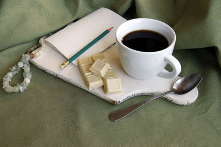 White cup with fresh coffee with a white bar of chocolate with whole hazelnuts. Breakfast on a white wooden shelf.