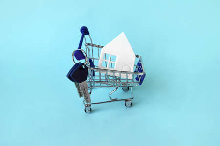 Mini shopping trolley with a white house and keys on a blue background. The concept of buying or renting a house, apartment, cottage and more.