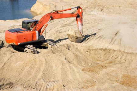 Orange excavator on a sand quarry. A lot of sand.