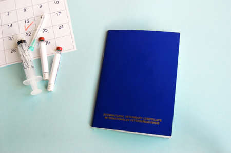Blue International veterinary passport, syringe and ampoule with liquid on a light blue background. Marked date on the calendar, concept of annual vaccinations for pets. Top view.
