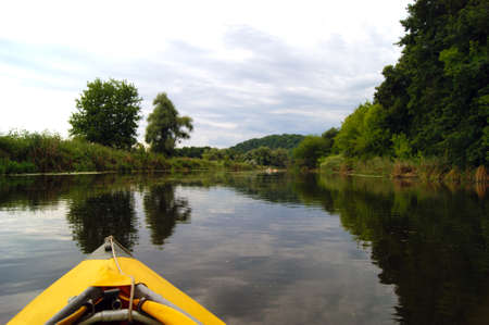 Kayak nose on the background of picturesque nature. Rowing in a yellow kayak in summer along the trees at the bank of Seversky Donets river.
