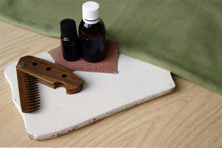 Male wooden comb for beard and hair, care oils on white desk. Compact folding comb that you can always take with you. Beard and hair care concept.