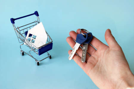 A hand holds the keys and next to it is a mini-trolley with a house made of white paper on a blue background. The concept of buying or renting a house, apartment, cottage and much more.