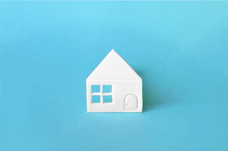 Little house of white paper on light blue background showing a concept for home and neighborhood. Stock Photo