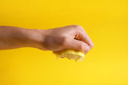 Hand crushes a piece of fresh lemon. Juice is wiped from a lemon. Sour.