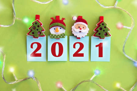 Photo greeting card happy new year 2021. Year 2021 on a green background and symbols of the winter holiday. Archivio Fotografico