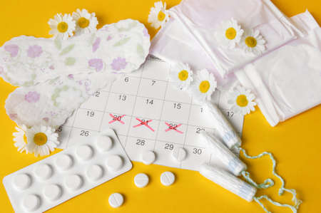 Menstrual pads and tampons on menstruation period calendar with chamomiles on yellow background. The concept of female health, personal hygiene during critical days. Stockfoto