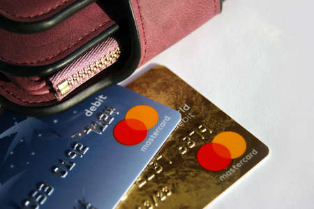 KHARKOV, UKRAINE - FEBRUARY 8, 2020: Close up of a Master Card Credit Card on white background. Nearby is a women's wallet Redactioneel