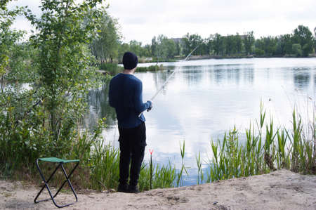 A lonely young guy goes fishing in the warm season. Interesting hobby. 免版税图像 - 154875530