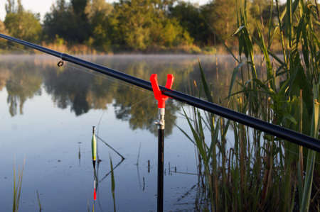 A slingshot for a fishing rod with a fishing rod on the background of the lake.
