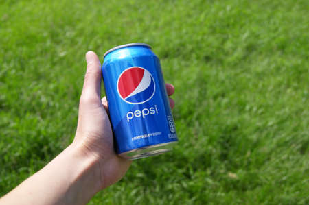 KHARKOV, UKRAINE - JUNE 12, 2020: Hand holds metal can of Pepsi on a background of green grass.