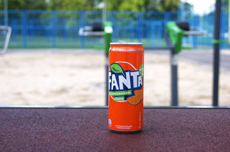 KHARKOV, UKRAINE - JUNE 12, 2020: A metal bottle of Fanta drink on the background of a street sports ground. Blurred background.