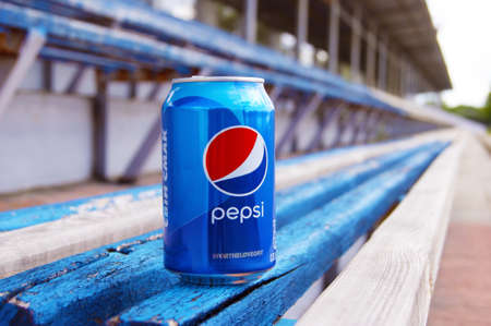 KHARKOV, UKRAINE - JUNE 12, 2020: A metal bottle of Pepsi drink stands on a wooden bench in a small stadium. Blurred background.