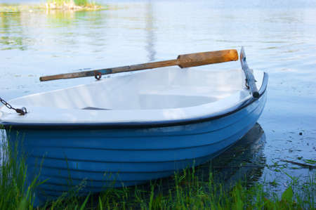 Lonely white-blue wooden boat with oars on the shore of a lake or river.
