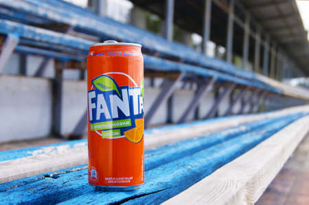 KHARKOV, UKRAINE - JUNE 12, 2020: A metal bottle of Fanta drink stands on a wooden bench in a small stadium. Blurred background.