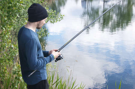 A lonely young guy goes fishing in the warm season. Interesting hobby.