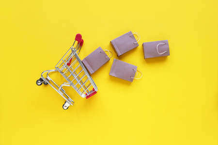 Mini shopping cart with small craft bags on the yellow background. Top view. The concept of shopping in stores and online.