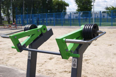 Weight plates on green equipment. Free outdoor gym. Concept of street workout