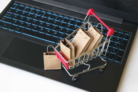 Mini shopping cart with small craft bags on the background of the keyboard. Online shopping concept. Convenience to shop without leaving home. Stock fotó