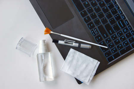 Keyboard, napkin, antiseptic and brushes on a white background. Cleaning concept. Office cleaning. Stockfoto