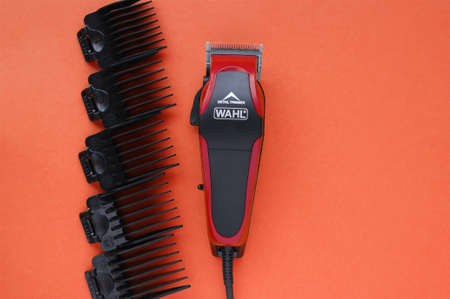 KHARKOV, UKRAINE - JULY 2, 2020: Hairdressers tool. Hair clipper WAHL close-up on a red background with nozzles of different sizes.