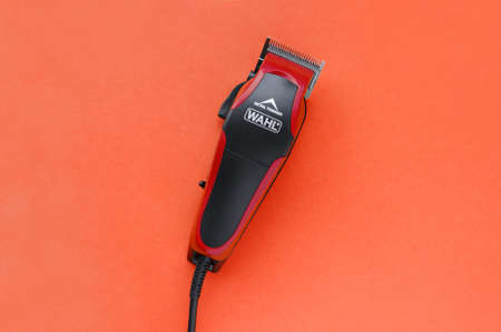 KHARKOV, UKRAINE - JULY 2, 2020: Hairdressers tool. Hair clipper WAHL close-up on a red background.