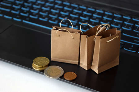 Small craft bags for purchases on the background of the keyboard. Online shopping concept. Convenience for shopping without leaving home.