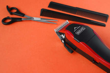 KHARKOV, UKRAINE - JULY 2, 2020: Hairdressers tool. Hair clipper WAHL close-up on a red background with scissors and combs. Redactioneel