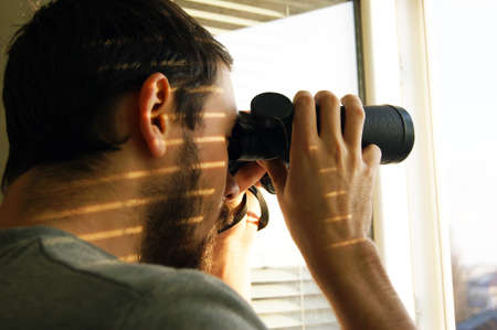 Young man standing looking through a glass window with binoculars as he watches something in the distance.